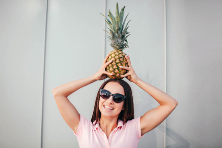 Positive girl in sunglasses stands and holds pineapple on her head. She keeps it in balance with hands. Girl looks on camea and smiles. Isolated on white and striped background. Stock Photo