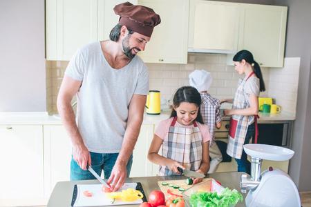 Papa se tient à table et coupe la tomate. Sa fille se tient près et coupe le concombre. Elle la regarde. Guy fait la même chose et sourit. La femme se tient avec son fils à la cuisinière et cuisinier.
