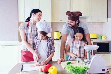 Glückliche Eltern stehen hinter ihren Kindern und lächeln. Sie sehen sich an. Kinder schneiden Gemüse separat. Standard-Bild