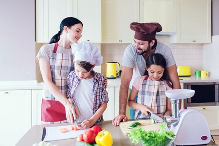 Happy parents stands behind their kids and smiling. They look at each other. Children cut vegetables separately.
