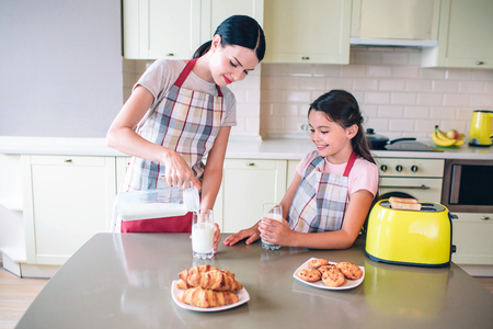 Woman stands at table and pouring milk in glass cup. Girl stands besides her mother and looks at it. She holds heer cup with hand. There are rolls and yellow toaster on table.