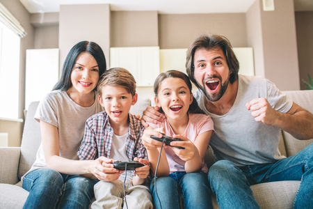 Amazing family sits on sofa. Children are playing on xbox. The game is intense. Guy rejoys. Girl is smiling as well. Mother helps to play her son.