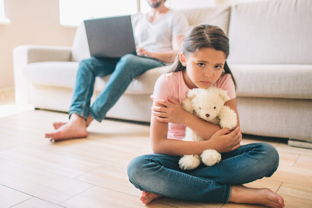 Small girl is sitting on floor. She is hugging her white bear toy. Girl looks to the right. She feels lonely. Her dad sits on sofa and work witth laptop.