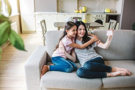 Beautiful woman and girl are posing. Adult holds phone and taking selfie. They are smiling. Stock Photo