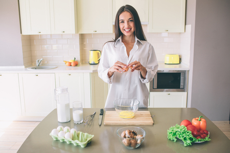 Attractive and gorgeoud young woman stands at the table in kitchen and looks on camera. She smiles. Girl holds coat of egg in hands. There is food on the table.