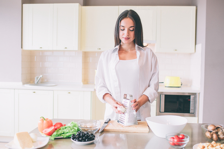 Beautiful girl stands at tabel and holds boiled egg close to grater. Stock Photo