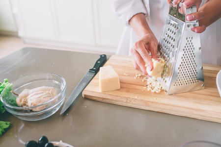 A picture of womans hands grating piece of cheese on grater. Knife is lying on table. Stock Photo
