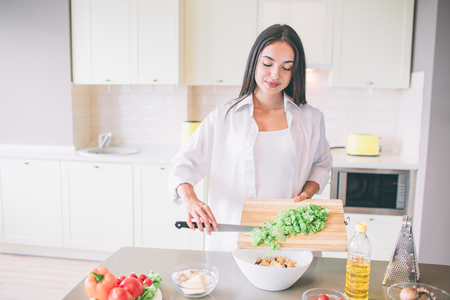 Careful and good-looking girl stands in kitchen and cooking salad.