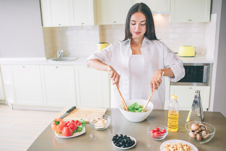 A picture of brunette mixing ingredients in white bowl with two wooden spoons. Standard-Bild - 106789192