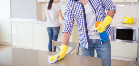 Cut view of man cleaning the surface of wood table. He wears yellow gloves. Guy uses blue rag for cleaning.
