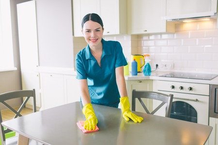 Smiling cleaner is standing and looking on camera. She cleans table. Girl wears special blue uniform. Woman works in apartment.
