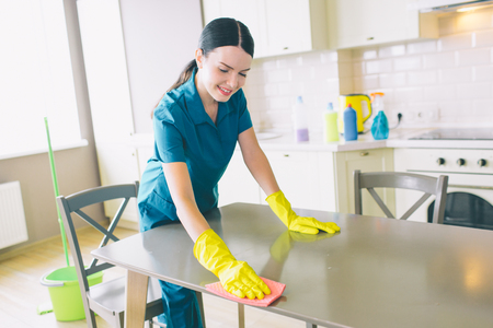 Positive female cleaner looks down and leans to table. She cleans it. Girl works in studio apartment in kitchen. She wears blue uniform and yellow gloves