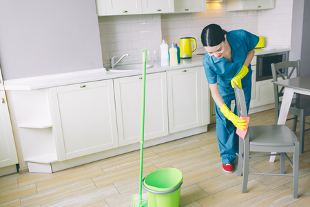 Concentrated and hard-working girl works in kitchen. She looks down and cleaning chair with orange rag. There are green bucket and mop on floor Stockfoto