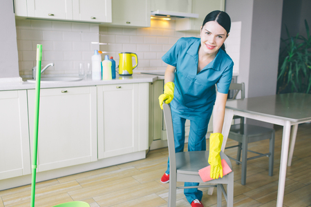 Morena positiva y agradable trabaja en la cocina. Limpia la superficie de la silla y mira la camerea. La mujer está sonriendo. Ella es alegre Foto de archivo