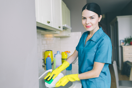 Horizontal portrait of girl washes dishes in sink. She is in kitchen. Brunette smiles and looks on camera. She wears blue uniform and yellow gloves Stockfoto