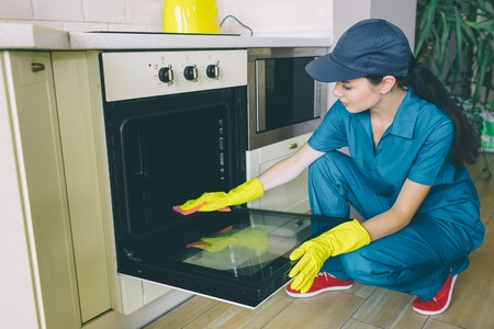Another picture of woman cleaning inside of stove. She washes the door. Girl holds it with hands. She works alone