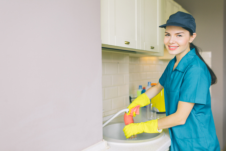 Positive and nice cleaner stands at sink and looks on camera. She washes water tube. Girl is cleaning in kitchen from dust and durt