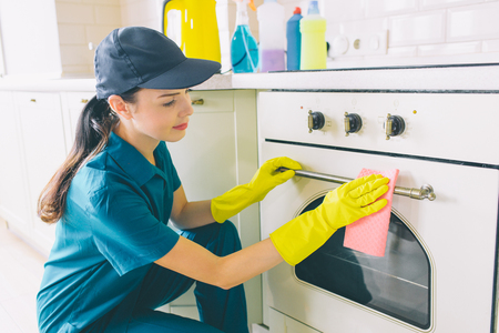 Nice and cheerful woman sits in squad position at stove and clean it door. She wears gloves and uniform for protection. Gir smiles a bit Stockfoto