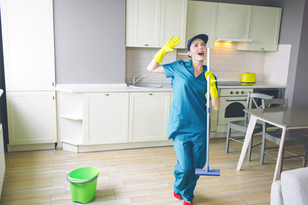 Fantastic woman stands in kitchen and holds mop in hands.