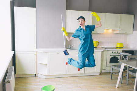 Funny cleaner jumps up in kitchen.