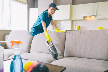 Serious woman stands and leans to sofa. She works with small vacuum cleaner. Girl wears uniform and gloves Stockfoto