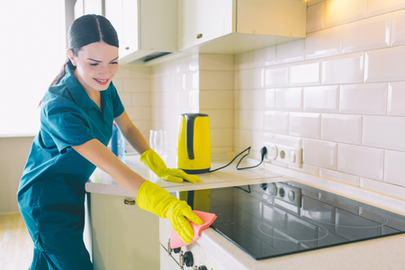 Cheerful cleaner works at stove. She cleans it with orange rag. Girl wears yellow gloves and blue uniform. She looks happy