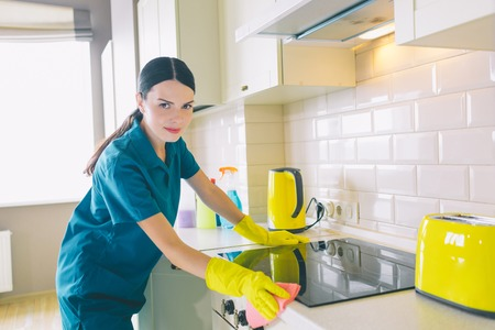 Calm and peaceful worker stands at stove and looks on camera. She cleans the surface of it. Girl poses. She has a rest Stockfoto