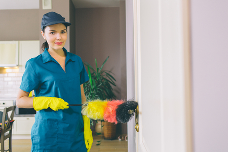 Brunette stands and poses on camera. She holds dust brush. Girl wears yellow gloves for protection and blue uniform Stockfoto