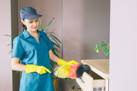 Another picture of girl stands and uses dust brush for cleaning drawer. She looks on it. Girl is concentrated. She wears blue uniform and yellow gloves Stockfoto