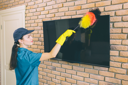 A picture of girl cleaning TV from dust. She ues dust brush. It is colorful. Girl works with pleasure