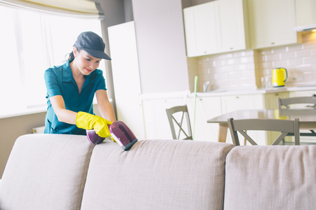 A picture of girl cleaning edge of sofa. She uses small vacuum cleaner. Woman is professional. She does work perfectly Stockfoto