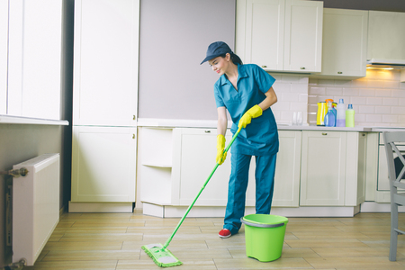 Professional cleaner is washing floor with green mop. THeere is bucket besides her. Girl wears uniform. She likes to clean
