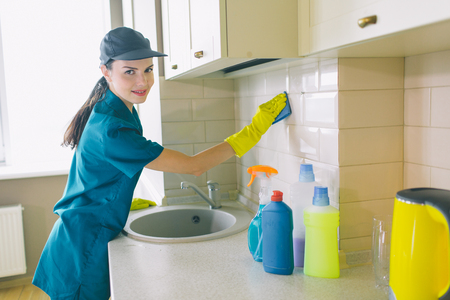 Nice girl stands and works in kitchen. She holds blue sponge. Girl looks on camera and smiles a bit. She is happy Stockfoto