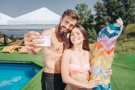 Nice picture of bearded guy and well-built girl standing and posing on camera. They take selfie on phone. People smile. Girl holds colorful mattress.