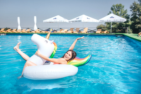 Happy and positive girl is lying on air mattress in the middle of swimming pool. She keeps hands and legs in air. Girl has some fun. She is there alone. Stock Photo