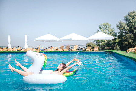 Happy and satisfied girl is lying on air mattress in the middle of swimming pool. She keeps hands and legs in air. Girl is relaxing. She has some rest.