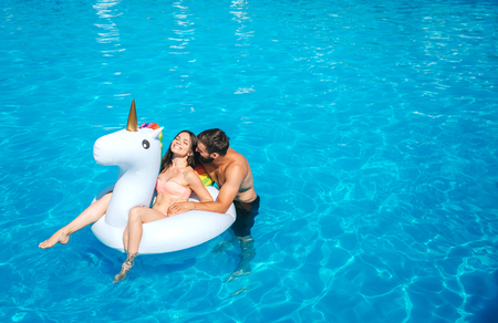 Nice and positive picture of man and woman swimming in pool. Girl sits on air mattress. She is laughing. Guy stands besides her and leans to her. They have some rest. Stock Photo