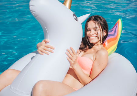 Nice and beautiful girl is lying on air mattress. It has shape of unicorn. Girl holds it with both hands and smiles. She looks on camera. Standard-Bild