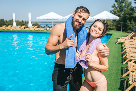 Beautiful man and woman stands at the edge of swimming pool and look on camera. They pose and smile. Girl and guy have towels around their necks. They look happy. 版權商用圖片
