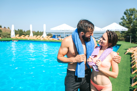 Another picture of well-built and slim couple standing together at the edge of swimming pool. They look at each other and smile. Guy nad girl have towels around their neck.