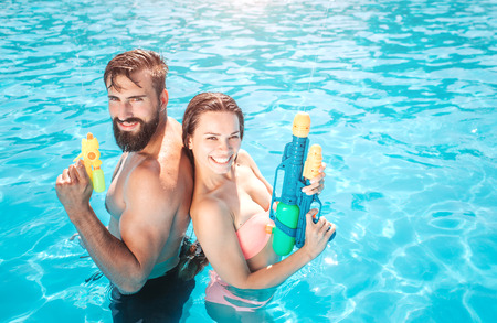 Godd-looking man and woman stand in swimming pool and look on camera. They pose and smile. People hold water gun in hands. They are ready to shoot.