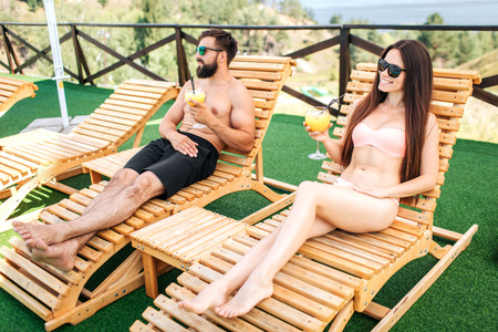 Guy and girl are resting on sunbeds and look to the left. They hold glasses of cocktails in hands. Girl is posing. They wear sunglasses.
