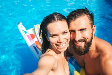 Nice and positive couple taking selfie and look on camera.