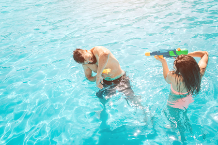 Funny picture of couple playing in swimming pool. Girl is shooting in guy from water gun.