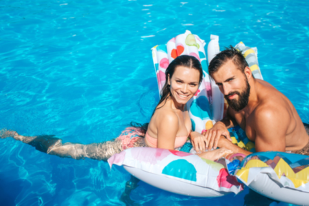 Nice and young couple is leaning on air mattress and look on camera. They pose. Girl is smiling. Guy blink. They look happy.