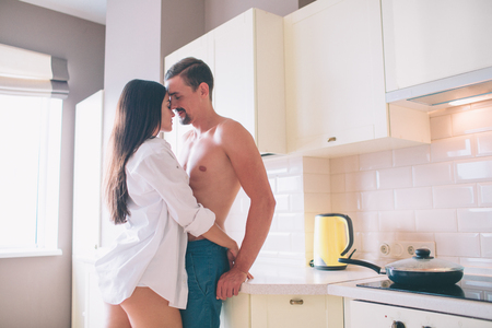 Amazing picture of man and woman standing close to each other. Girl embraces guy. She holds hands on his buttocks. They touches each others forehead. People are in love. Guy leans to table. Stock Photo