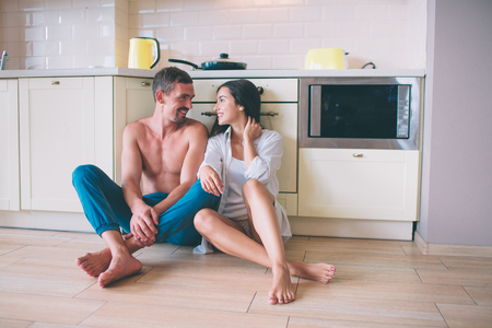 Lovely couple is sitting on floor in kitchen and look at each other. They keep their hands crossed. People are smiling. They look happy.
