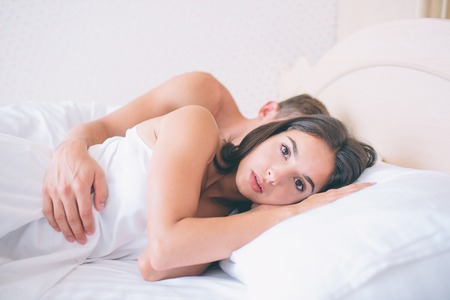 Serious girl is lying in bed and looks forward on camera. She is not sleeping. Bed is white. Guy lseeps behind her. He keeps his hand on girl.