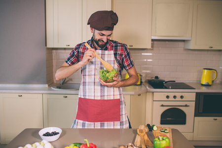Positive and happy cook stands in kitchen and holds glass bowl with salad. He mixed it with wooden spoon. Young man looks down at it.
