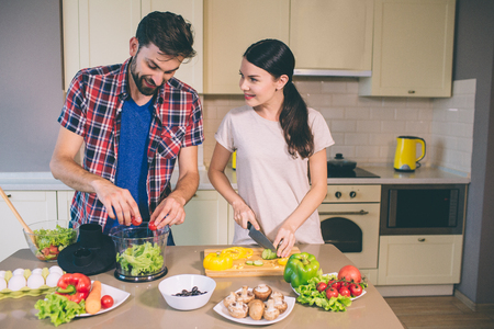 Nice couple works together in kitchen. She cuts mushrooms and look at guy. He is juicying tomatoes into plastic bowl and look at it. They are concentrated.